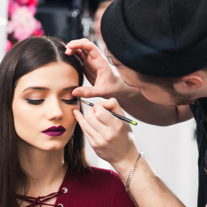 professional makeup artist applying editorial makeup look on client model