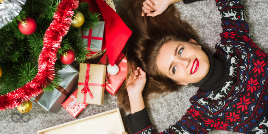professional makeup artist lying under christmas tree with gifts