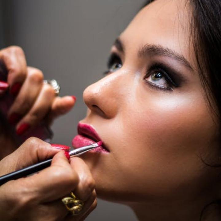 starting your own makeup business. A makeup artist applying makeup to a model