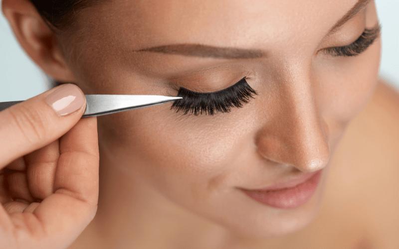 applying false eyelashes to female model's eye