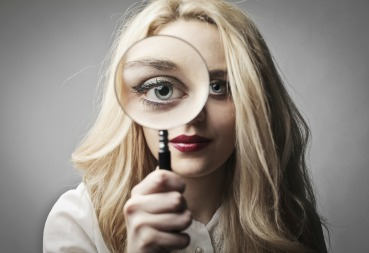 Woman Looking into Magnifying Glass