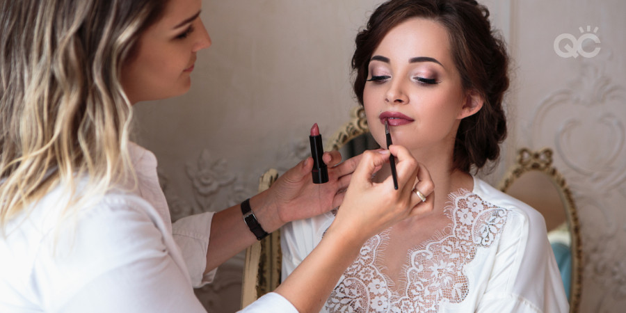 certified makeup artist applying red lipstick to her client