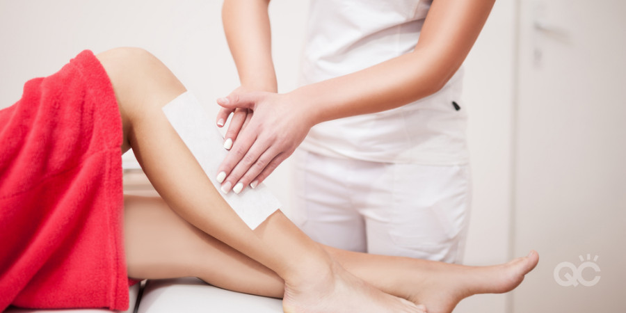 esthetician waxing leg of a client at a salon