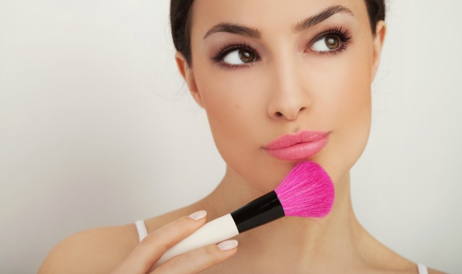 Woman thinking with professional makeup artistry brush