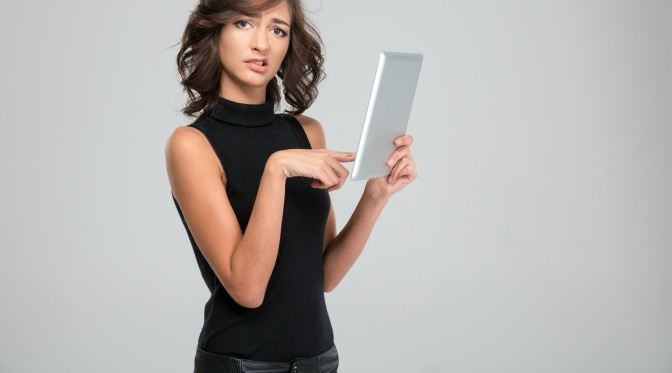 Confused young woman holding tablet