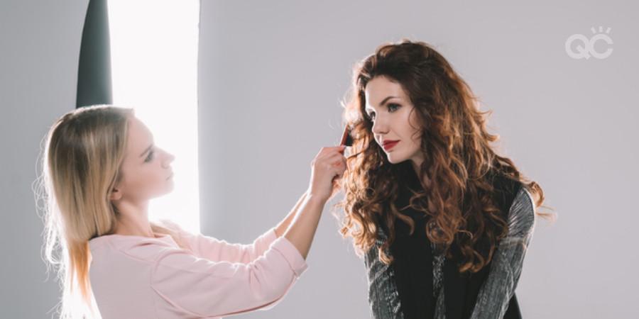 makeup artist applying makeup on model for a photoshoot
