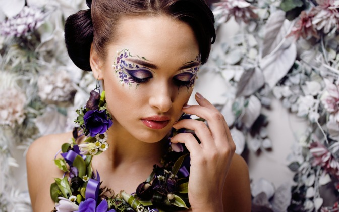Model with floral makeup, outfit, and backdrop
