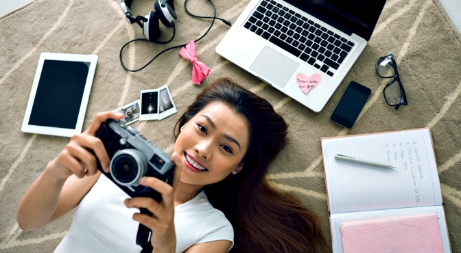 Girl holding camera and lying on bed with laptop, notebook, and headphones