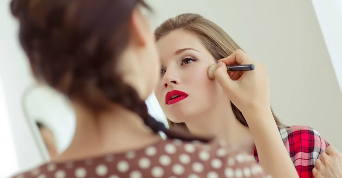 Makeup artist applying blush to a client