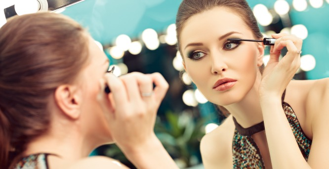 Woman applying mascara in a mirror