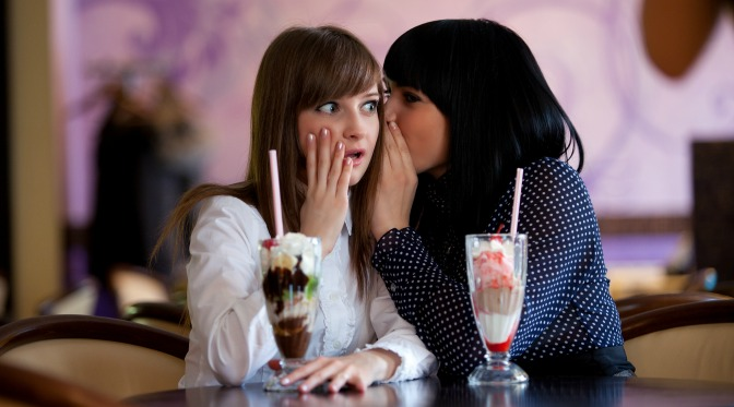 Two women sharing secrets in a diner