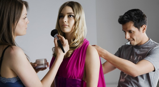Makeup artist and stylist working on model