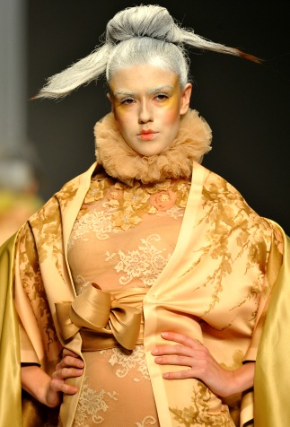 Model with elaborate makeup and hair on the runway