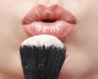 Makeup artist blowing loose powder off her brush