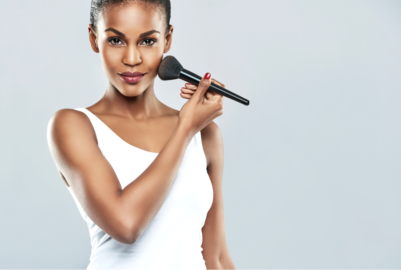 confident woman applying makeup with brush