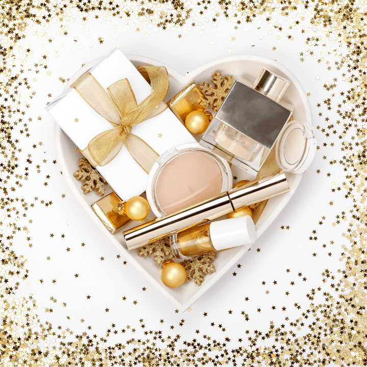 heart-shaped box, surrounded by gold glitter, filled with makeup and beauty presents