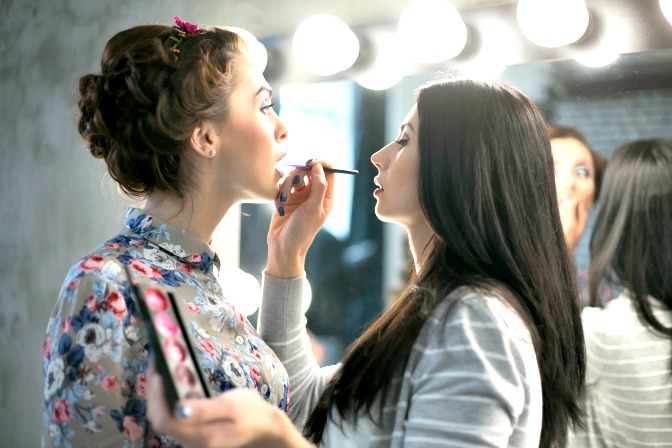 Makeup artist applying makeup on young model during NY Fashion Week