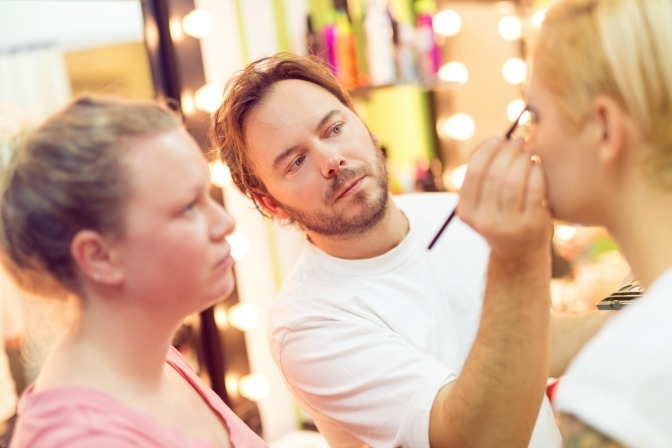 Special effects makeup artist applying makeup on film set