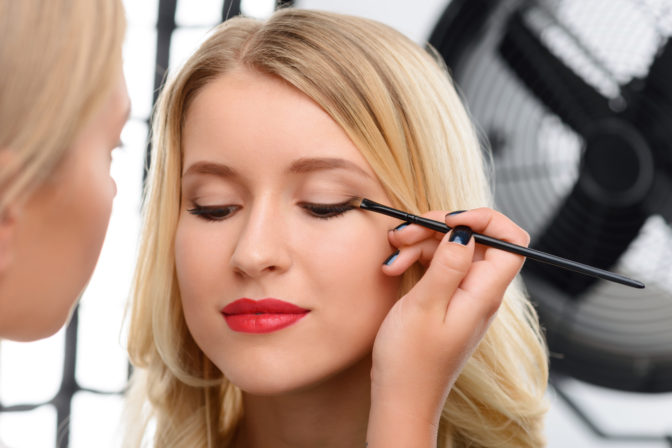 Women working as a professional makeup artist in studio