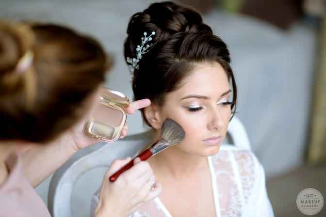 Bridal makeup artist applying look on day-of