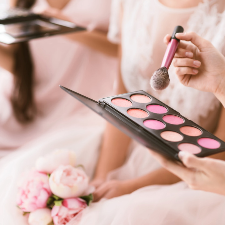 bridal makeup artist with blush palette applying to bridesmaids