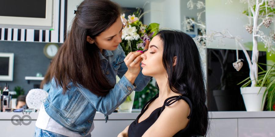 makeup artist applying holiday makeup on her client in her makeup studio