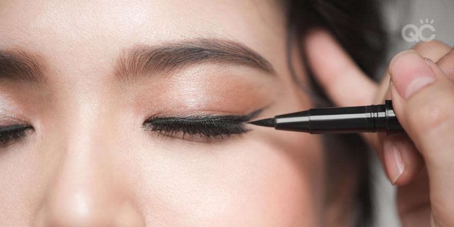 makeup artist practice applying eyeliner on model