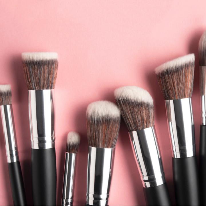 makeup brushes on pink background - makeup salary budgeting for your makeup kit and makeup business