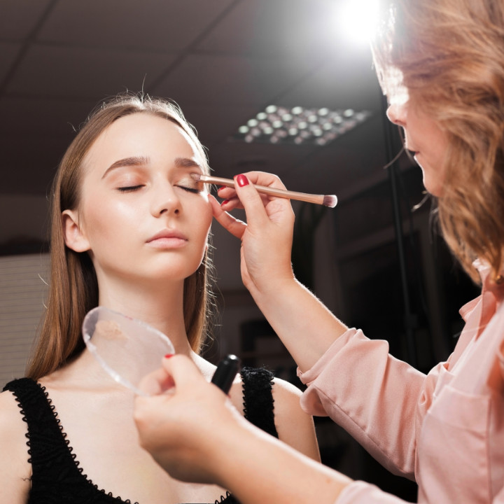 makeup artist certification holder working on model