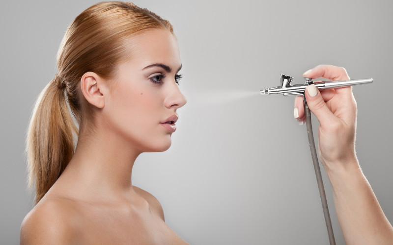 airbrush makeup artistry - spraying model's face with airbrush