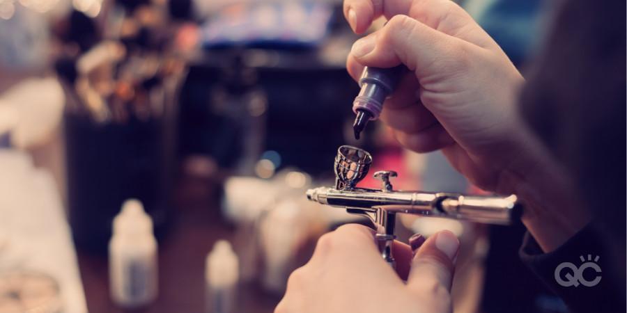 makeup artist putting airbrush makeup into airbrush gun
