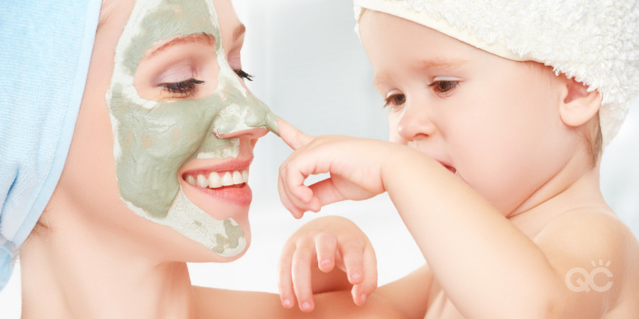 clay mask on mom with her baby touching her face
