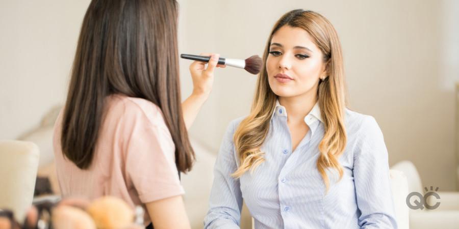 makeup artist practicing makeup techniques on model applying blush