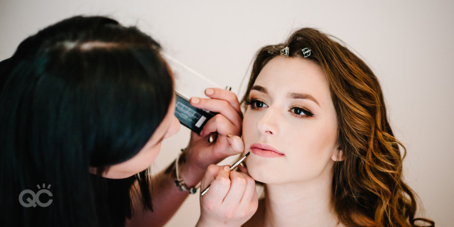 makeup artist applying lip gloss from makeup artist kit