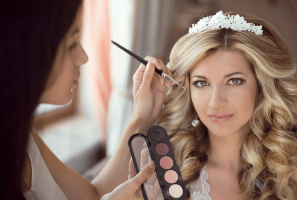 makeup artist equipped with a makeup palette applying makeup on bride