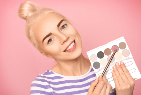 beautiful beauty blogger holding eyeshadow palette in front of pink backdrop