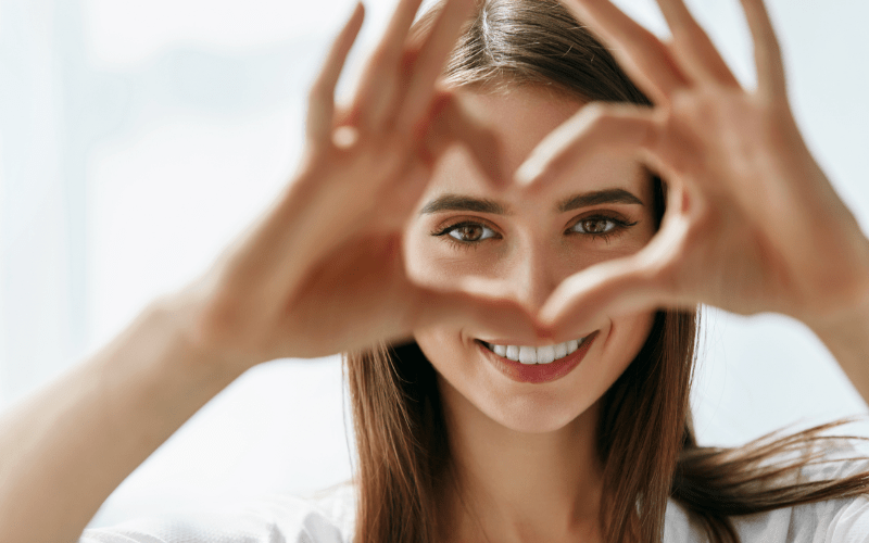 smiling woman making heart symbol with fingers