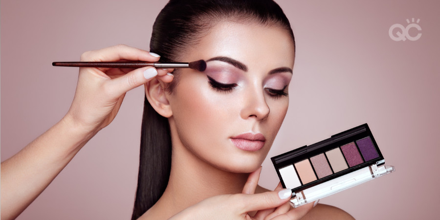 makeup items you don't need - model wearing eyeshadow with eyeshadow palette held up