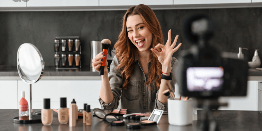 girl with makeup products filming herself doing tutorial