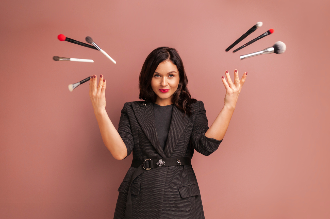 makeup items you don't need - woman throwing brushes away