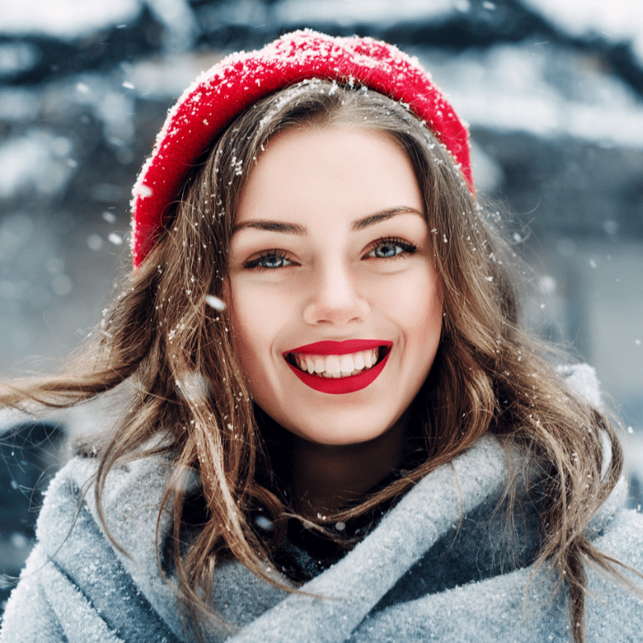 model outside in the snow, with beautiful brows, lashes, and red lip makeup