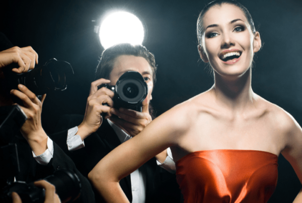 female celebrity smiling for the cameras while paparazzi take pictures