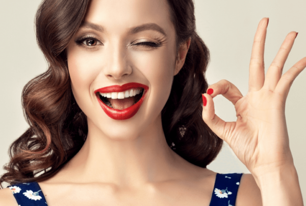 woman with pinup-style hair and makeup winking and giving OK sign with hand