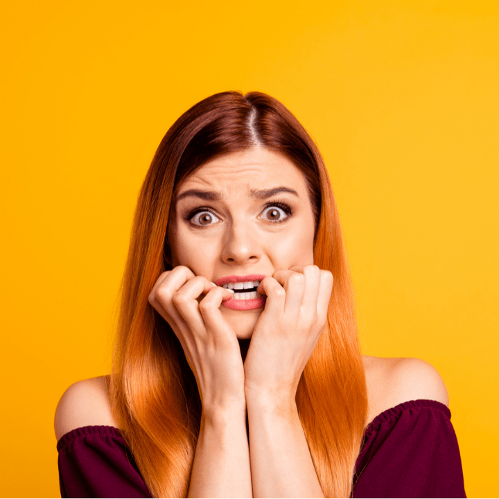 scared worried woman in front of yellow background