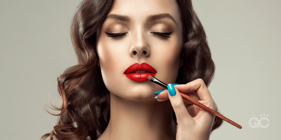 upclose shot of models face, and mua's hand applying product to her lips