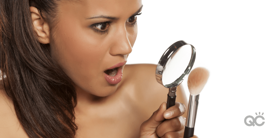 woman shocked as she looks at makeup brush through magnifying glass