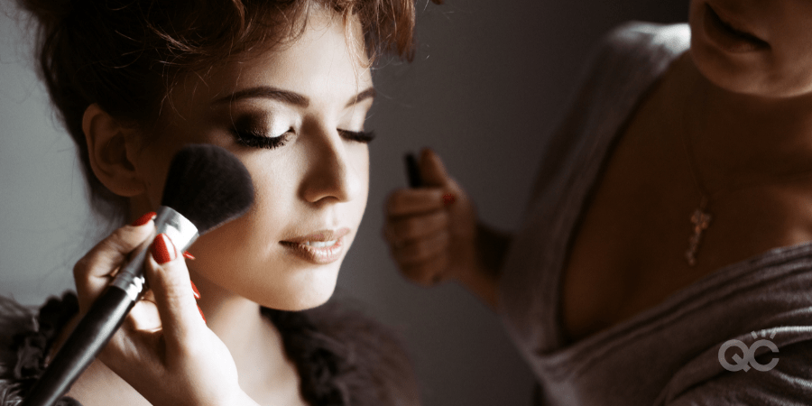 upclose of model's face, with MUA applying powder to cheek with brush