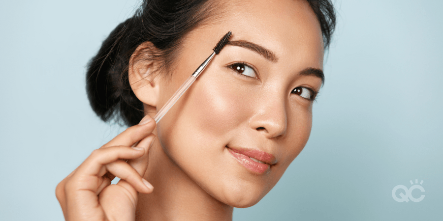 woman brushing eyebrows with a spoolie