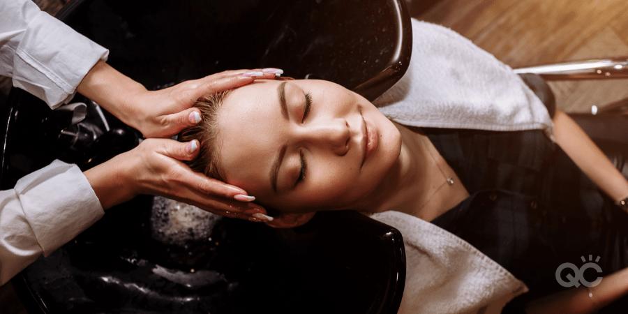 hair stylist washing client's hair