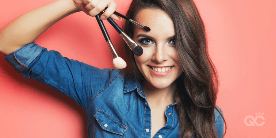 smiling woman holding 3 different makeup brushes